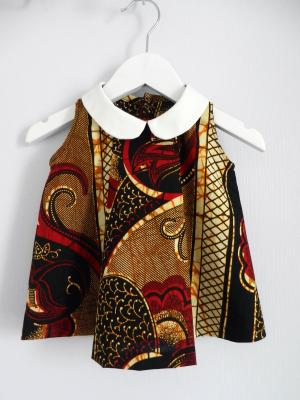 Robe sans manches en wax rouge, noir et jaune, avec plis sur le devant et col claudine blanc